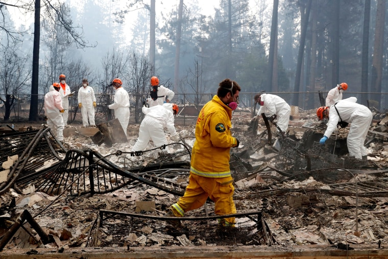 Image: A volunteer search and rescue crew from Calaveras County comb through a home destroyed by the Camp Fire in Paradise