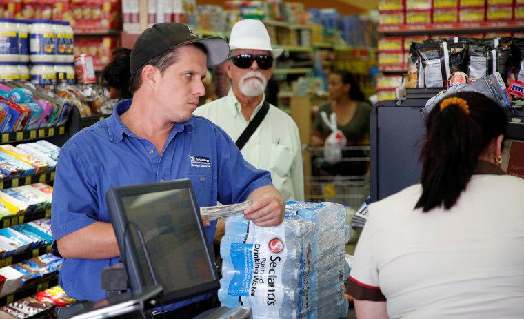 A shopper waits to purchase water in Sedano's Supermarket in the Little Havana neighborhood in Miami