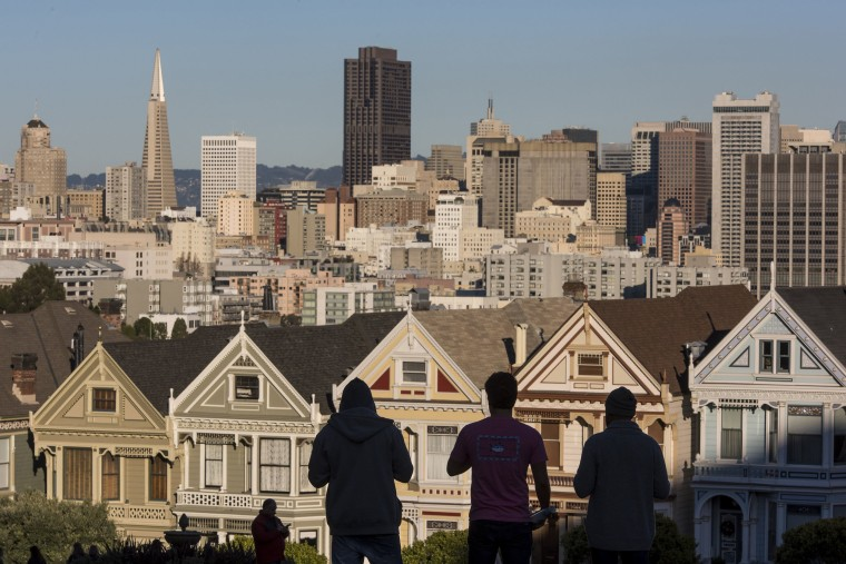 Image: The silhouettes of pedestrians stand in front of Victorian homes and the downtown skyline in San Francisco