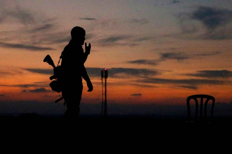 Image: The silhouette of an Israeli soldier is pictured in the southern Israeli town of Sderot