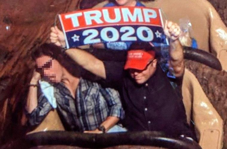 Dion Cini holds a Trump 2020 banner at Walt Disney World.