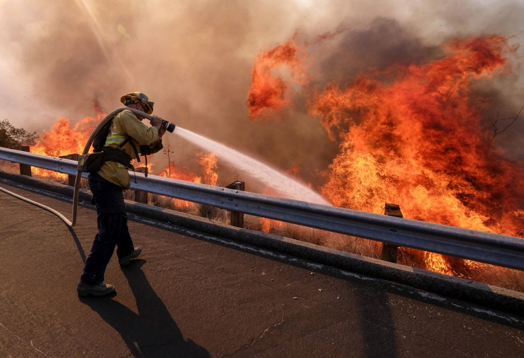 A firefighter battles a fire along the Ronald Reagan (118) Freeway in Simi Valley, California, on Nov. 12, 2018.