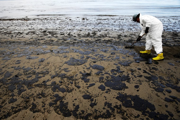 A worker removes oil from sand at Refugio State Beach, north of Goleta, California, on May 21, 2015.