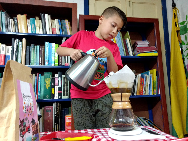 Julian Murillo, 8, pours a chemex-method coffee during the Cafeteritos after school program in the library in Marsella, Risaralda, Colombia.