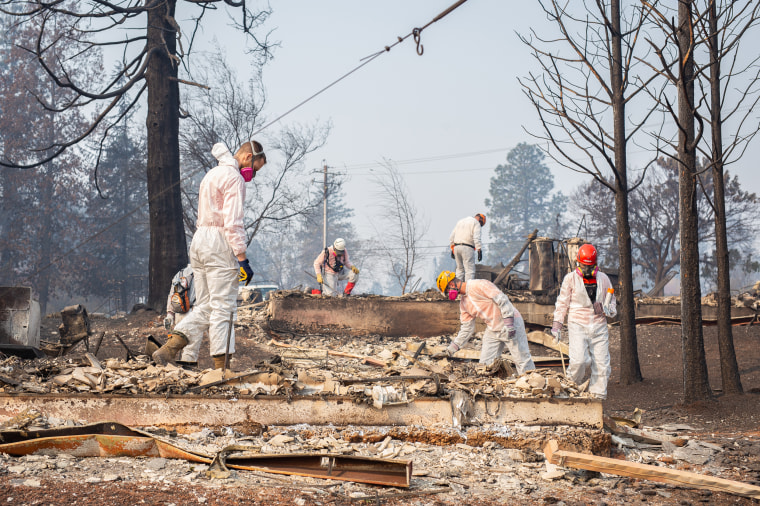 Search and rescue teams work amid a bleak landscape of charred home remains in Paradise, California on Friday.