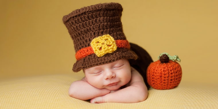 Smiling four week old newborn baby boy wearing a crocheted Pilgrim hat. He is sleeping on a gold blanket next to a crocheted pumpkin.; Shutterstock ID 343622084; Purchase Order: today.com; Segment/Job: parents; Client/Licensee: Tyler