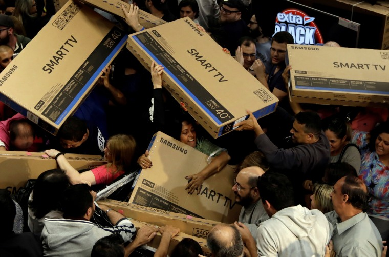 Image: Shoppers reach out for television sets as they compete to purchase retail items on Black Friday at a store in Sao Paulo