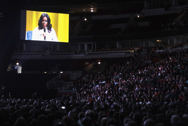 Image: Guests watch as Oprah Winfrey interviews former first lady Michelle Obama as she kicks off her 'Becoming'  arena book tour