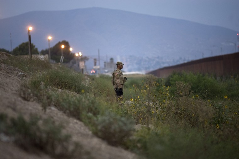 Image: A U.S. military policeman watches as other troops install concertina wire on top of the U.S.-Mexico border wall