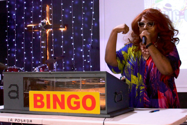 Joe Uvalles, a.k.a. Beatrix Lestrange, pulls a bingo number at the migrant charity event.