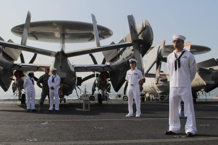 Image: U.S. Navy sailors stand guard on the flight deck of U.S. Navy aircraft carrier USS Ronald Reagan during its visit to Hong Kong