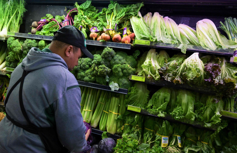 A produce worker stocks shelves near romaine lettuce at a Whole Foods supermarket in Washington on Nov. 20, 2018.