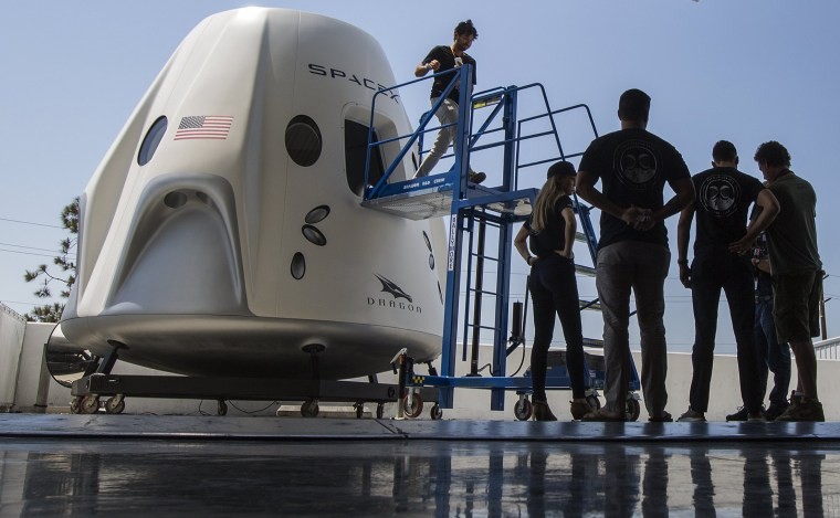People explore a mock up of the Crew Dragon spacecraft