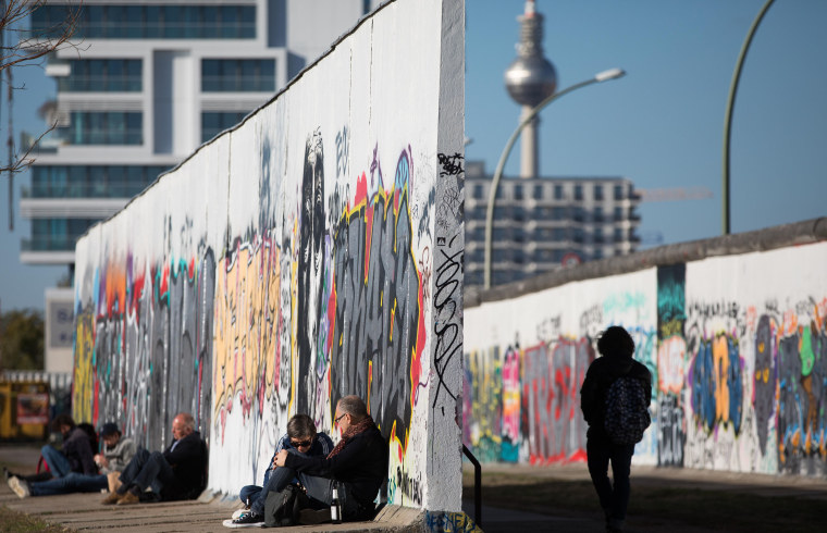 Image: People sit along the Berlin wall at the East Side Gallery in Berlin, as the landmark television tower is seen in the background