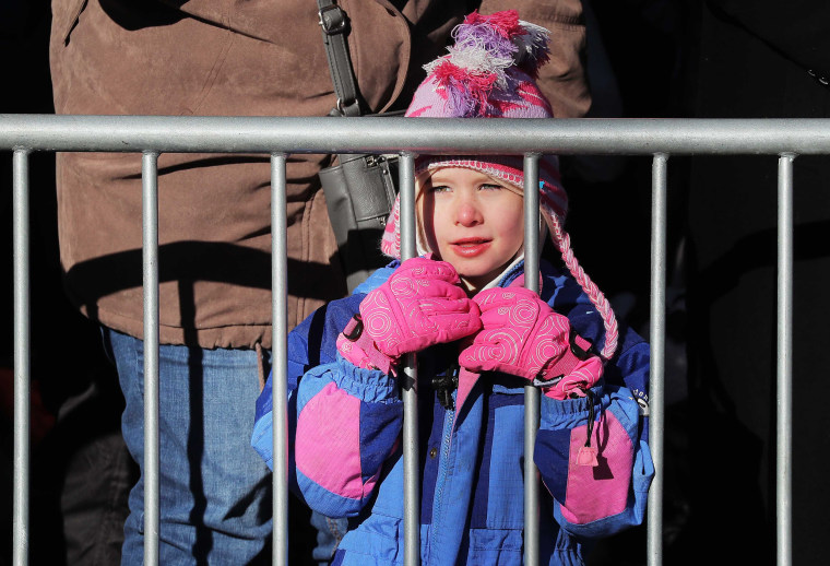 Image: A child watches floats pass from behind a barricade during the Macy's Thanksgiving Day Parade in Manhattan