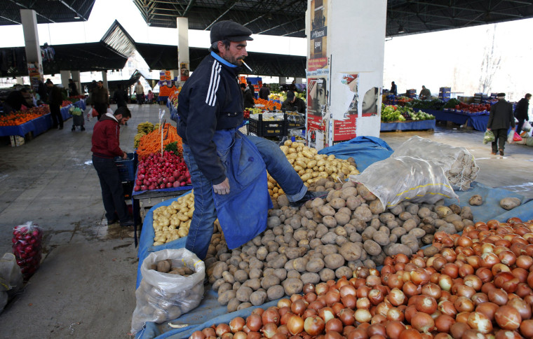 Image: A vendor sells potatoes and onions in an open market in central Ankara
