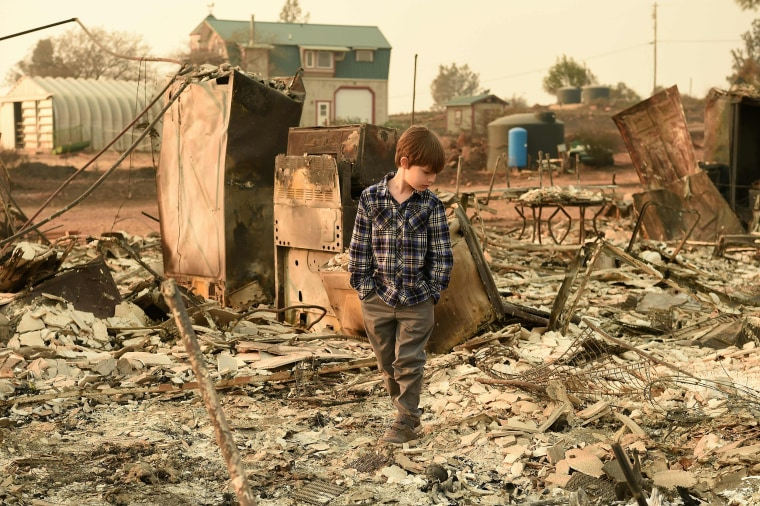 Image: Jacob Saylors, 11, walks through the burned remains of his home in Paradise, California on Nov. 18. The family lost a home in the same spot to a fire 10 years prior.