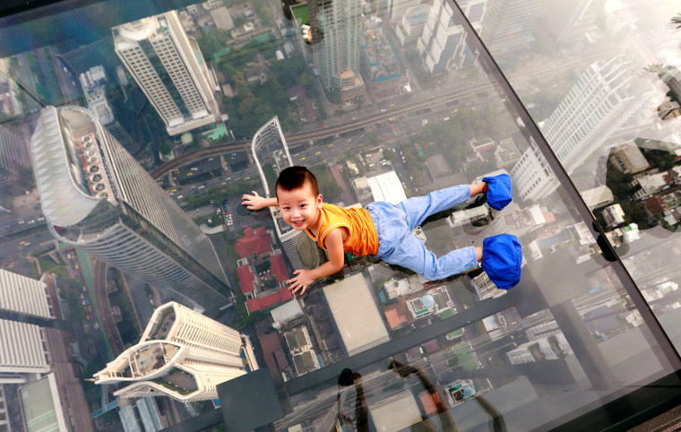 Image: A boy plays on the glass at Thailand's first skywalk in Bangkok