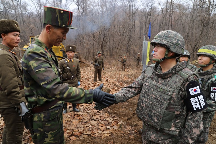 Image: A South Korean military officer (R) and a North Korean military officer shake hands during an operation to reconnect a road across the Military Demarcation Line inside the Demilitarised Zone (DMZ) separating the two Koreas