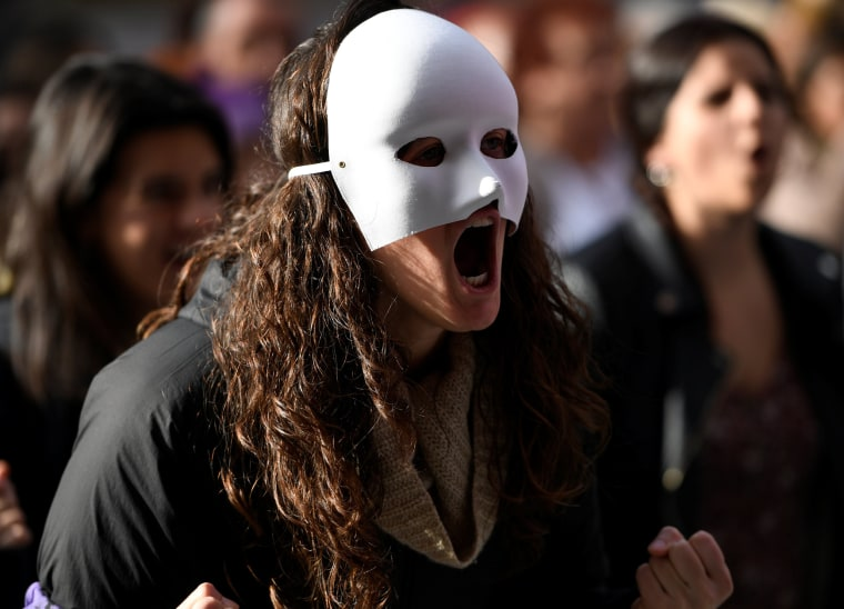 Image: A woman with a mask participates in a rally against gender-based and sexual violence against women in Gijon