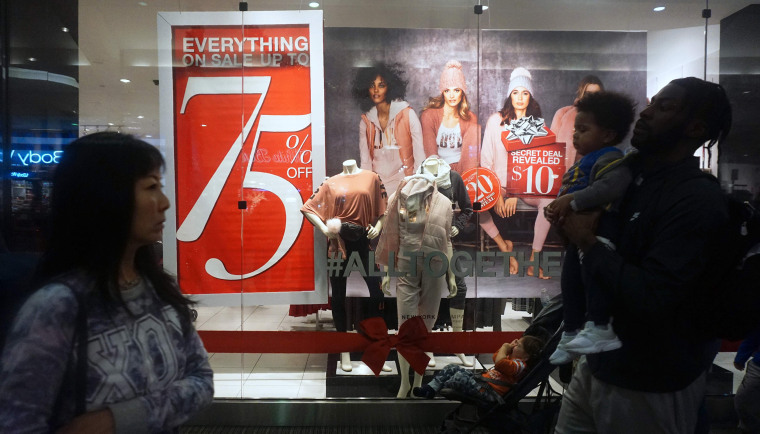 Image: Shoppers walk past sale signs for Black Friday at a mall in Montebello