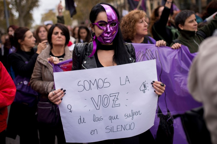 "Image: A woman holds a placard reading ""We are the voice of those who suffer in silence"""