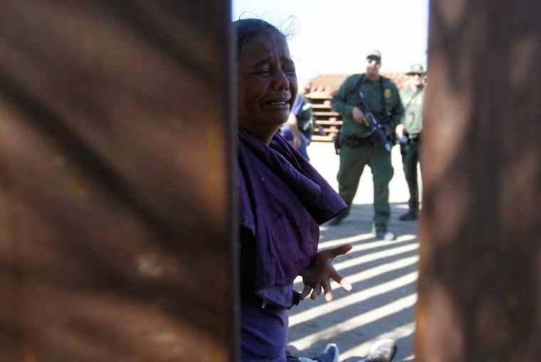 Image: A migrant woman, part of a caravan of thousands from Central America trying to reach the United States, reacts as a group of U.S border patrol officers detained her with along with others after entering the United States illegally from Tijuana