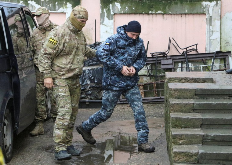 Image: A member of Russia's FSB security service escorts a detained Ukrainian navy sailor on Nov. 27