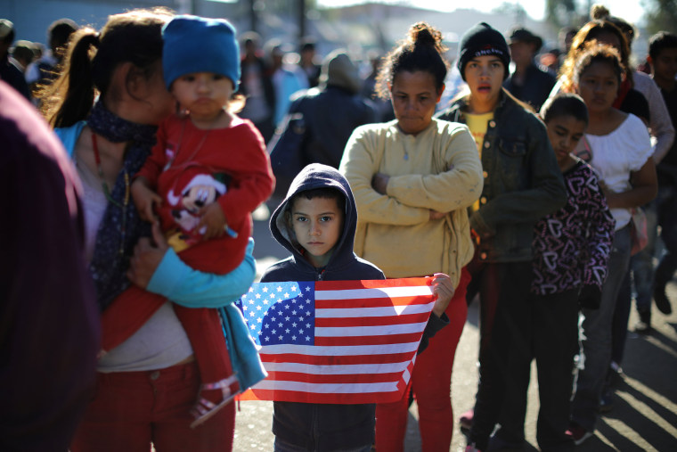 Image: Marie Orellana, 28, and her seven-year-old son Angel, from Honduras, part of a caravan of thousands of migrants from Central America trying to reach the United States, queue for food outside a temporary shelter in Tijuana