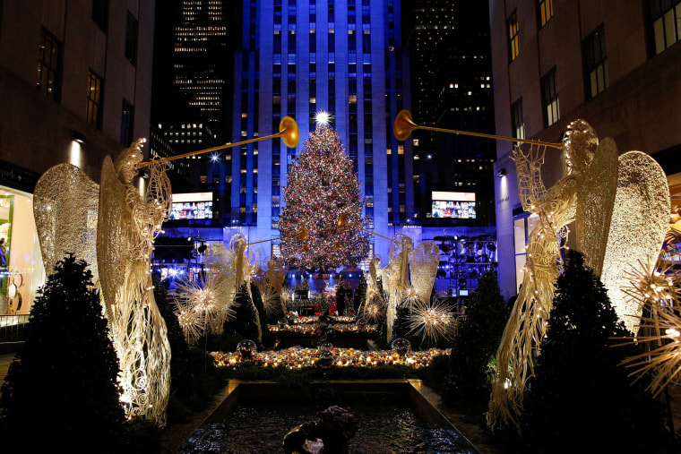 Image: People watch the Christmas tree lighting at Rockefeller Center in the Manhattan borough of New York