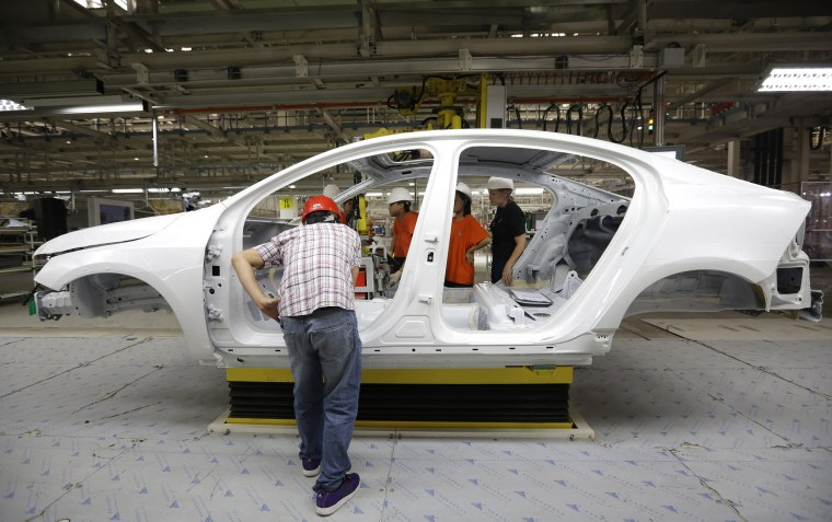 Image: Workers prepare to assemble parts of a Volvo car at an assembly line of the new Volvo automobile manufacturing plant in Chengdu