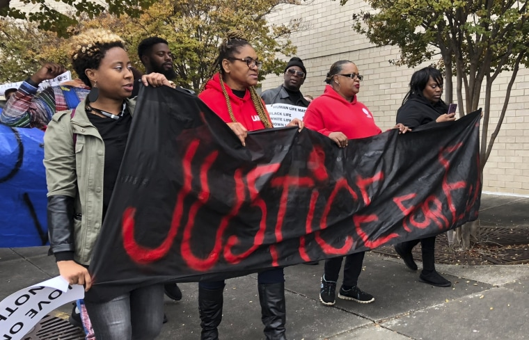 "Protesters carry a sign reading ""Justice for E.J."" outside of the Riverchase Galleria mall in Hoover, Alabama, on Nov. 24, 2018."