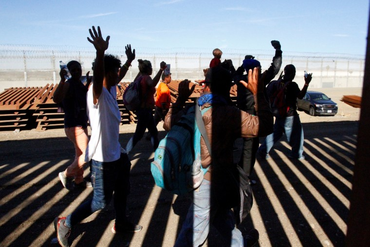 A group of migrants hold up their hands as border patrol officers detain them in Tijuana, Mexico, on Nov. 25, 2018.