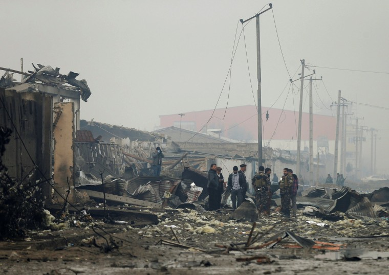 Image: Afghan secutity forces inspect the site of a car bomb attack in Kabul