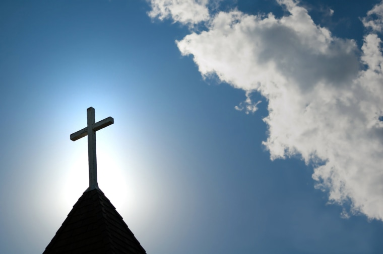 Image: Easter morning with the sun behind a church steepl cross.