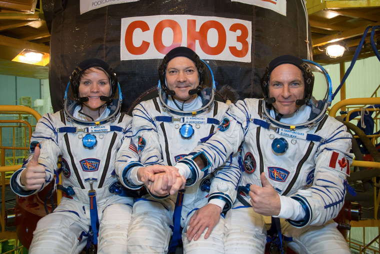 NASA astronaut Anne McClain (left), Russian cosmonaut Oleg Kononenko (center) and David Saint-Jacques of the Canadian Space Agency (right) pose in front of their Soyuz MS-11 spacecraft.
