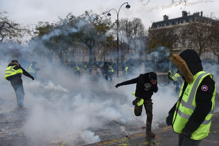 Image: Demonstrators try to avoid riot police smoke grenades