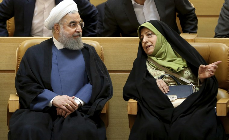 Iranian President Hassan Rouhani listens to Masumeh Ebtekar during a conference