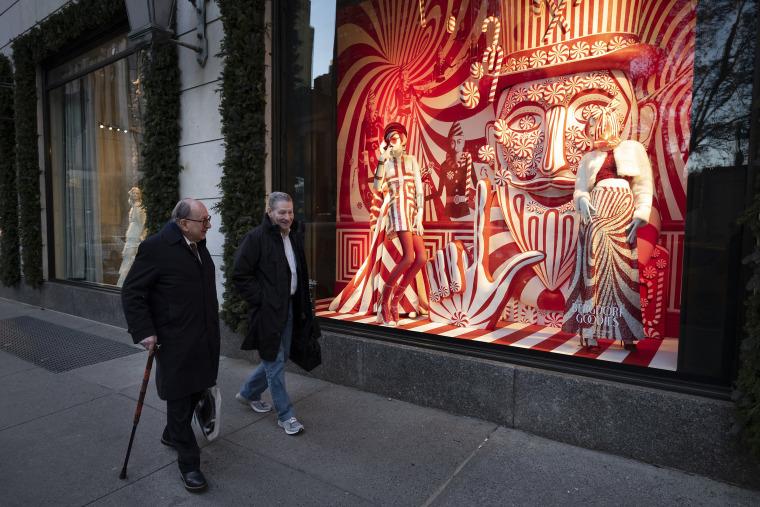 Men walk past a holiday window at Bergdorf Goodman,on Dec. 5, 2018, in New York.