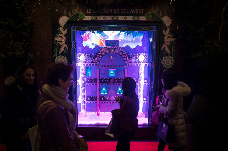 People look at the Christmas windows on the opening night at the Galeries Lafayette department store in Paris on November 7, 2018.