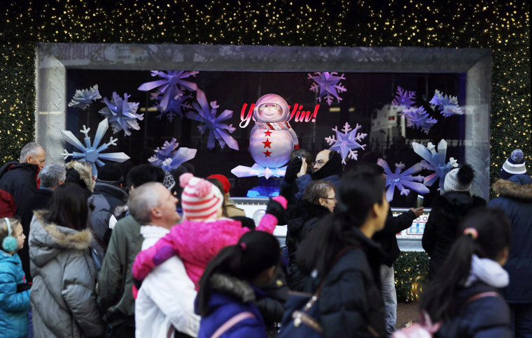 People stop to admire MACY's Herald Square holiday windows as bargain hunters seek low price deals during 'Black Friday' holiday shopping in New York, New York, on November 23, 2018.