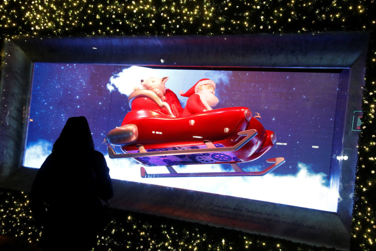 Image: A visitor looks toward the Christmas holiday window displays at Macy's Herald Square in Manhattan, New York City