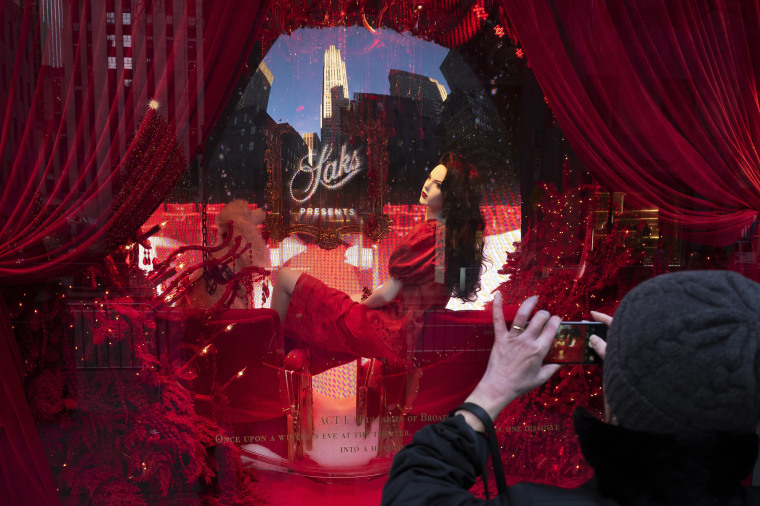 A woman photographs a holiday window at Saks Fifth Avenue, Wednesday, Dec. 5, 2018, in New York.