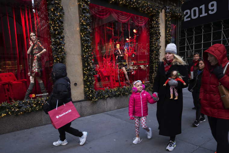 People walk by holiday windows at Saks Fifth Avenue, Wednesday, Dec. 5, 2018, in New York.