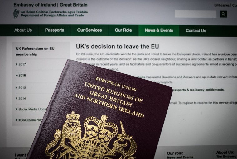 Image: A UK passport in front of a webpage for the Irish Embassy in Wells, England