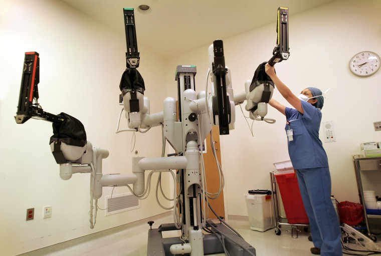 Image: A registered nurse adjusts the robotic arms before an automated calibration of the Da Vinci robot that will be used in surgery at the Helford Clinical Research Hospital in Duarte