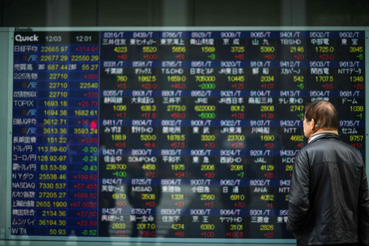 Image: A man looks at a stock indicator board of the Tokyo Stock Exchange in Tokyo