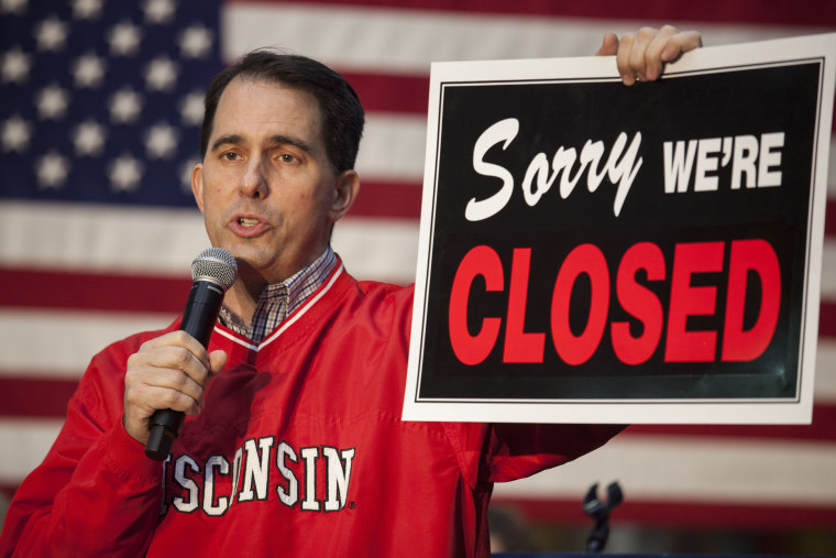 Governor Scott Walker holds a sign as he speaks to supporters at a rally the night before the midterm elections in Waukesha, Wisconsin, on Nov. 5, 2018.