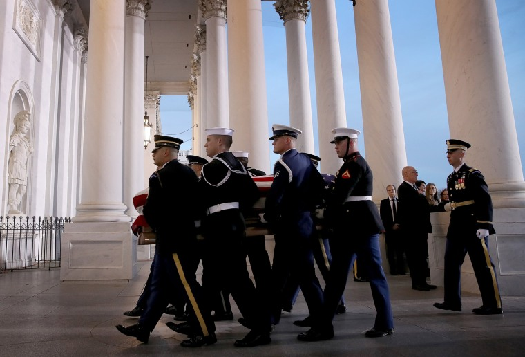 Image: A military honor guard team carries the casket of former U.S. President George H. W. Bush into the U.S. Capitol in Washington