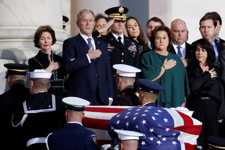 Image: Former President George W. Bush and other family members watch as the flag-draped of former President George H.W. Bush is carried by a joint services military honor guard to lie in state in the rotunda of the U.S. Capitol